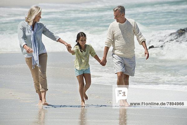Mädchen beim Spaziergang mit ihren Großeltern am Strand