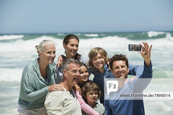 Glückliche Mehrgenerationen-Familie beim Selbstporträt mit dem Handy am Strand