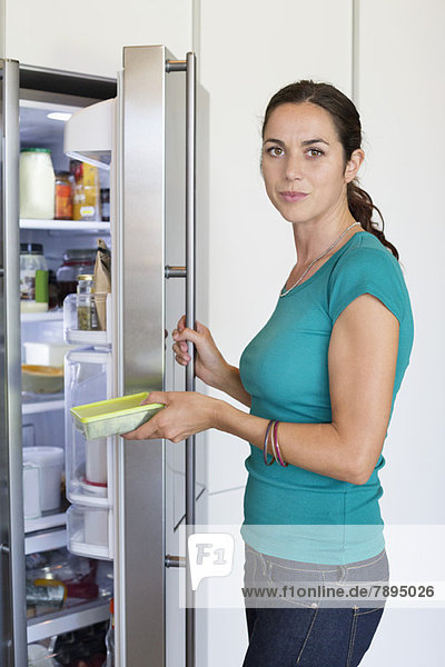 Woman putting food in a refrigerator