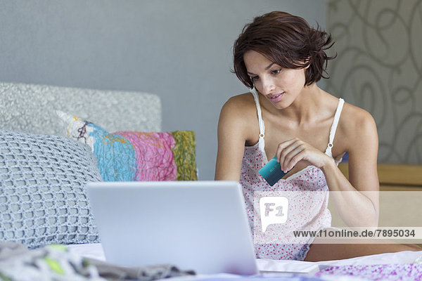 Woman holding credit card and working on a laptop