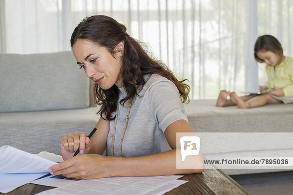 Woman doing paperwork with her daughter using a digital tablet in the background