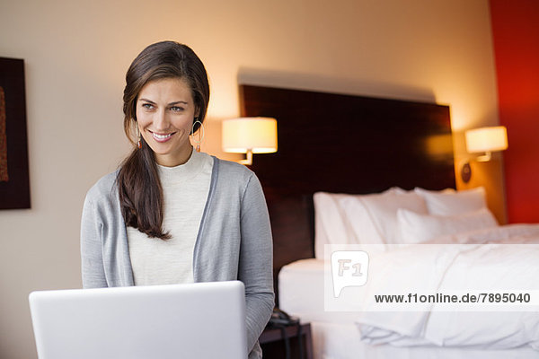 Woman using a laptop in a hotel room and smiling