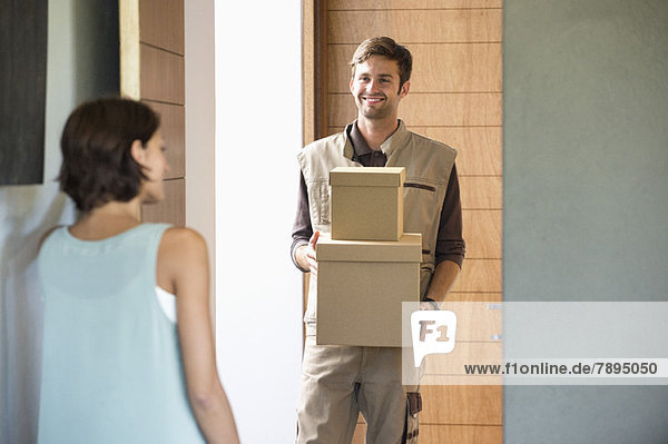 Delivery man delivering parcel to a woman