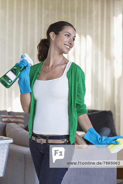 Woman holding cleaning equipment and smiling