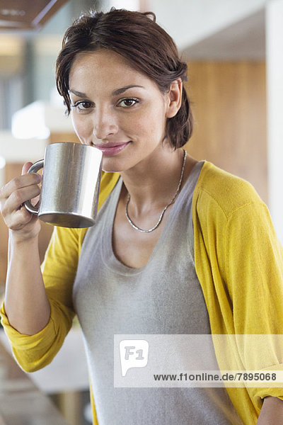 Woman drinking herbal tea in the kitchen