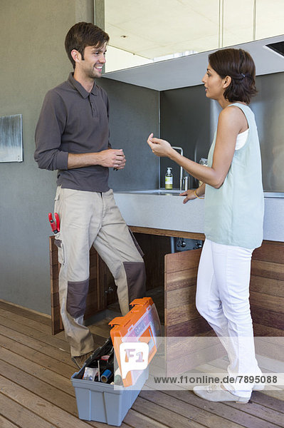 Woman discussing with a repairman in kitchen