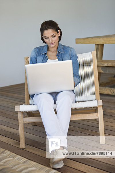 Woman sitting on a chair and using a laptop
