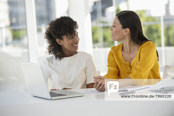 Zwei Frauen lächeln sich an.