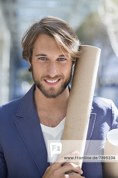Porträt eines Architekten mit Papierrollen und Lächeln