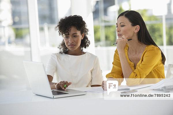 Zwei Freundinnen beim Betrachten eines Laptops zu Hause