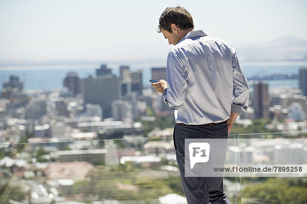 Auf der Terrasse stehender Mann mit dem Handy