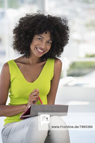 Porträt einer lächelnden Frau mit einem digitalen Tablett