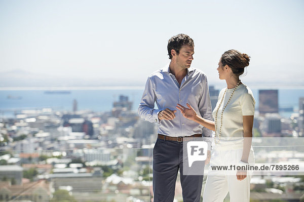 Paar diskutiert auf einer Terrasse mit Stadt im Hintergrund