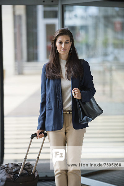 Businesswoman holding a suitcase in a hotel lobby