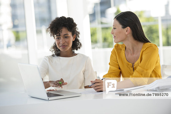 Freundinnen bei der Arbeit am Laptop zu Hause