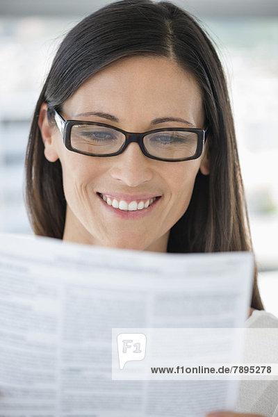 Nahaufnahme einer Frau  die ein Dokument liest und lächelt