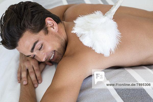 Mann auf dem Bett liegend mit Staubwedel auf dem Rücken