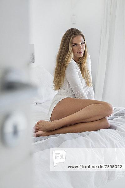 Frau auf dem Bett sitzend