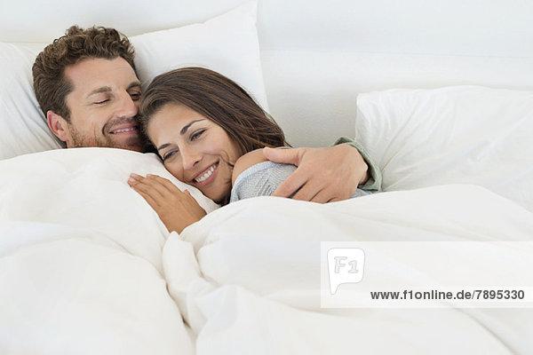 Lächelndes Paar auf dem Bett liegend
