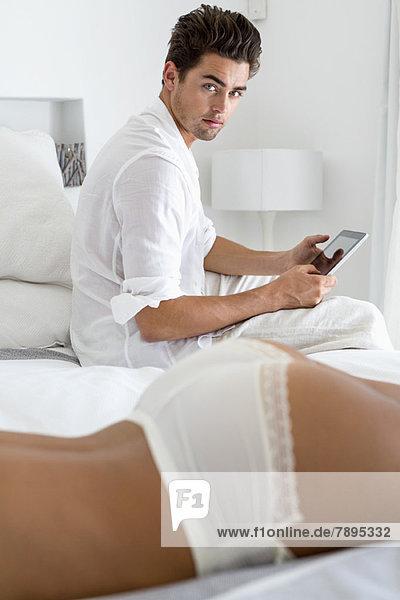 Mann schaut auf seine oben ohne Freundin  die auf dem Bett liegt.