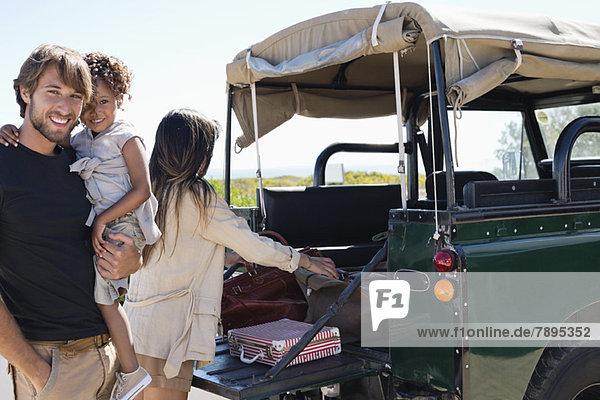 Glückliche Familie neben einem SUV