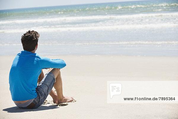 Mann am Strand sitzend