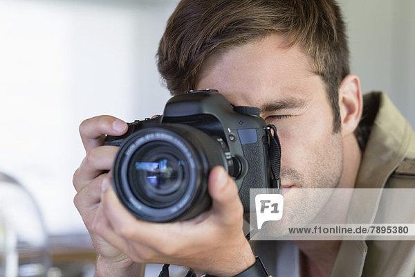 Nahaufnahme eines Mannes  der mit einer Kamera fotografiert.