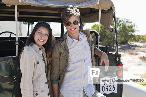 Porträt eines lächelnden Paares neben einem SUV