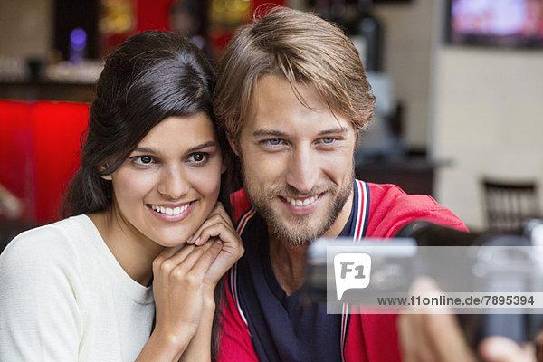 Paare filmen sich mit einer Heimkamera.