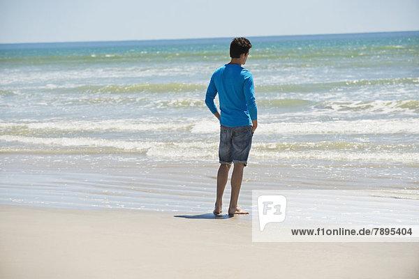 Mann steht am Strand und schaut auf das Meer.