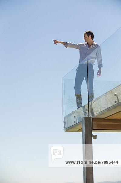 Mann auf der Terrasse stehend und zeigend