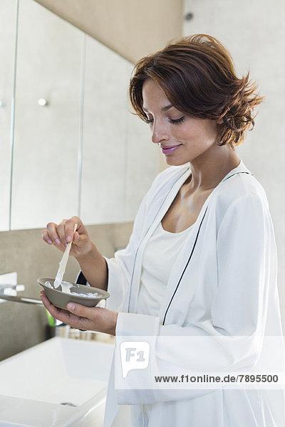 Frau beim Mischen von Haarfärbemitteln im Bad