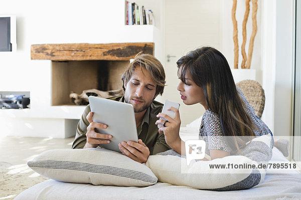 Auf dem Bett liegendes Paar mit elektronischen Geräten