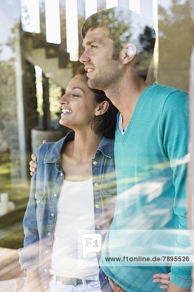 Lächelndes Paar steht hinter einer Glaswand