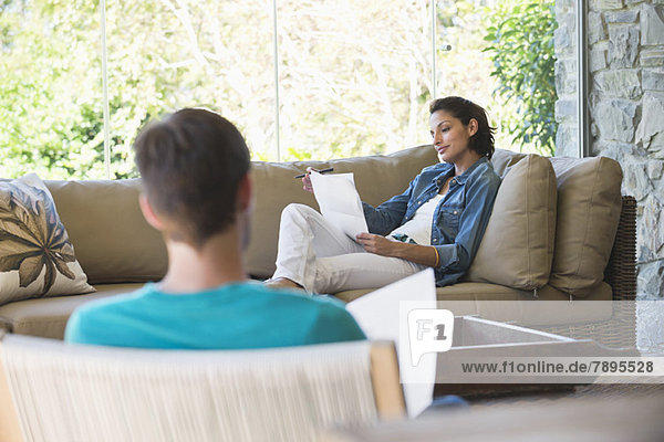 Frau sitzt auf einer Couch und prüft Rechnungen