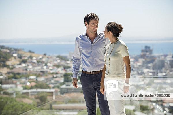 Ein Paar schaut sich auf einer Terrasse mit der Stadt im Hintergrund an.