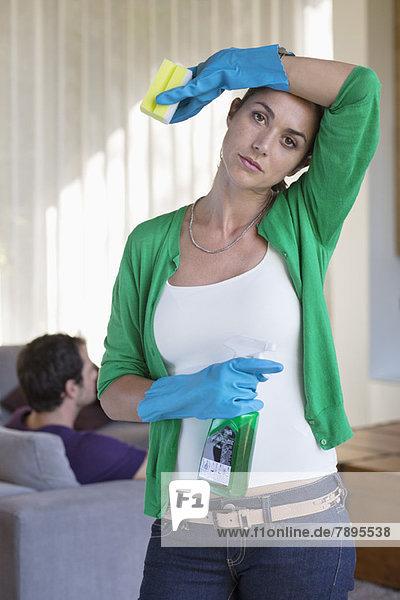 Frau hält Reinigungsgeräte in der Hand und sieht müde aus  wenn ihr Mann auf einer Couch sitzt.