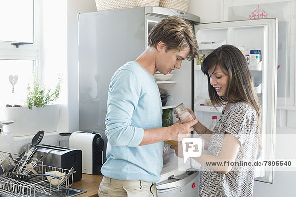 Paar  das vor einem Kühlschrank in der Küche auf Lebensmittel schaut