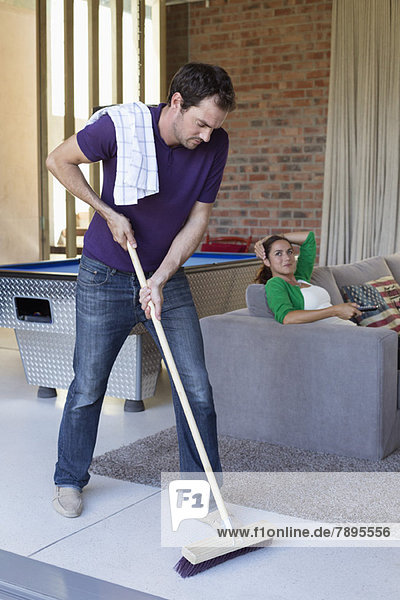 Mann putzt den Boden mit einem Wischmopp und seiner Frau beim Fernsehen im Hintergrund