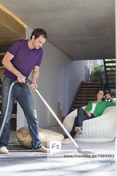 Mann  der das Haus mit einem Staubsauger putzt  während seine Frau auf einem Sitz sitzt.