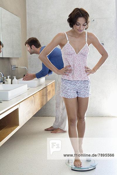 Frau misst ihr Gewicht auf einer Waage mit ihrem Mann in einem Badezimmer.