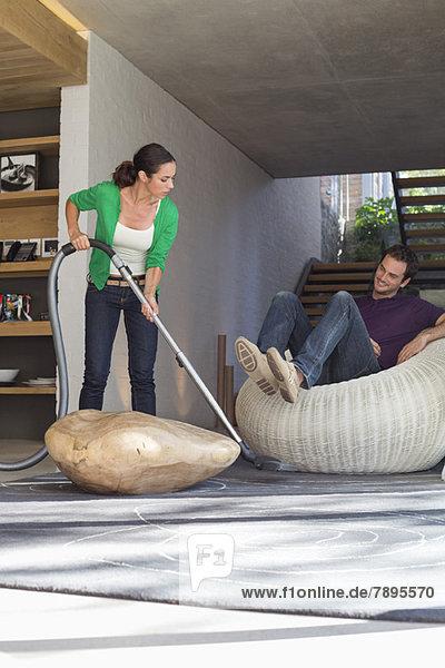 Frau  die das Haus mit einem Staubsauger putzt  während ihr Mann auf einem Sitz sitzt.