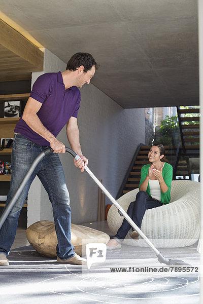 Mann,  der das Haus mit einem Staubsauger putzt,  während seine Frau auf einem Sitz sitzt.