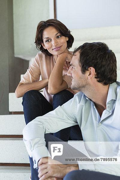 Paar auf der Treppe sitzend und lächelnd