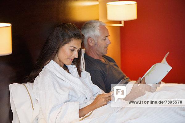 Frau,  die ein digitales Tablett benutzt,  während ihr Mann in einem Hotelzimmer ein Buch liest.