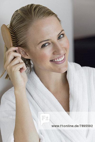 Porträt einer lächelnden Frau beim Haareputzen