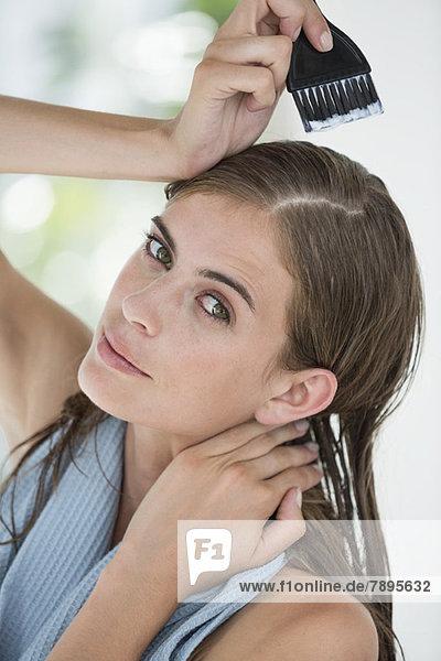 Porträt einer Frau beim Haare färben