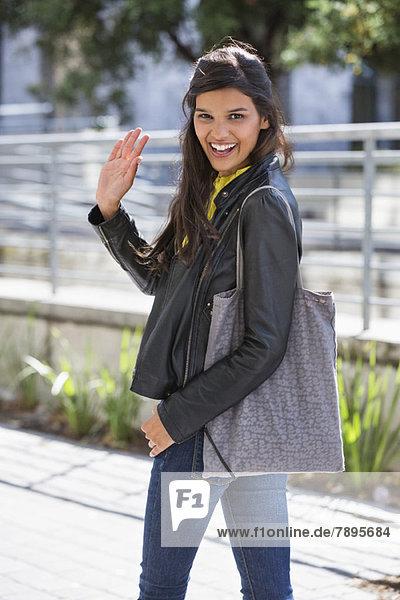 Porträt einer Frau  die mit der Hand wedelt und lächelt
