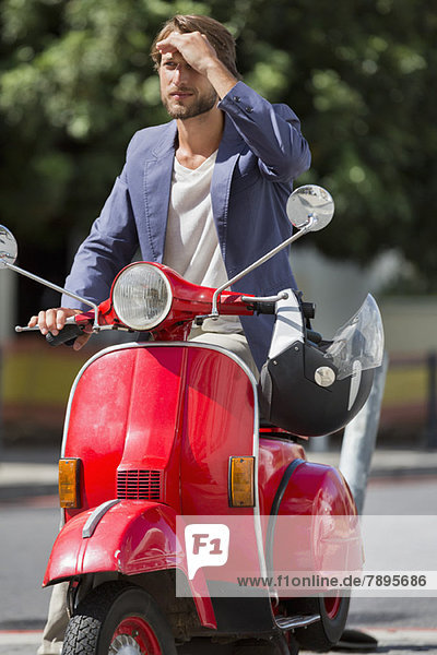 Man sitting on a scooter shielding his eyes