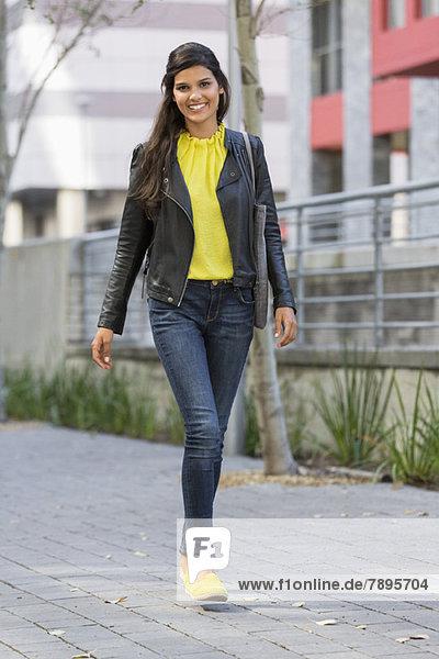 Porträt einer Frau  die auf der Straße geht und lächelt